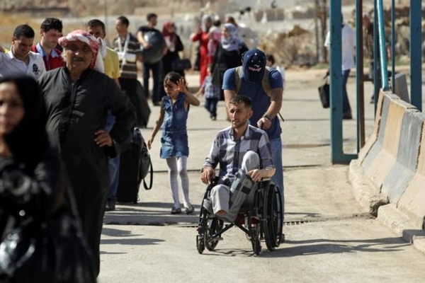 A Syrian pushes a man on a wheelchair as others carry their belongings while crossing back into Syria at the Syrian-Turkish border crossing of Bab al-Hawa in Idlib province, Syria September 23, 2015. REUTERS/Khalil Ashawi
